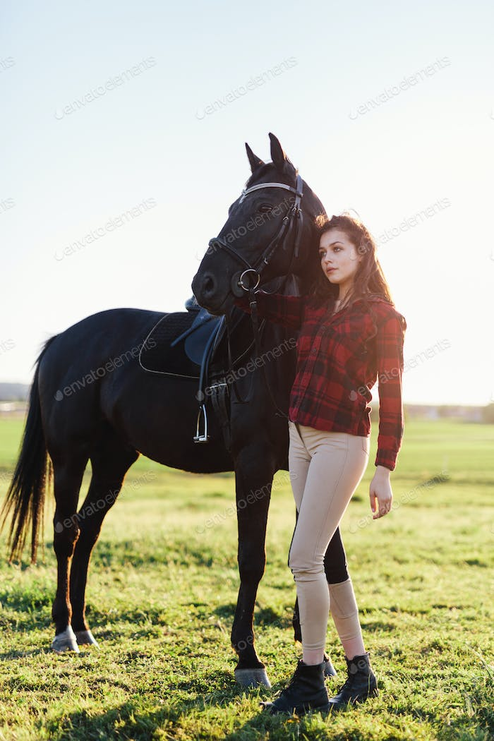 Black horse and an attractive young woman