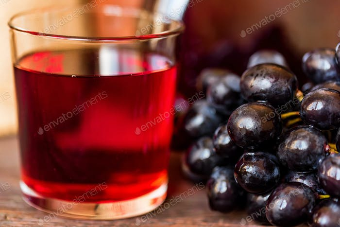 Red grape juice in glass and grapes close