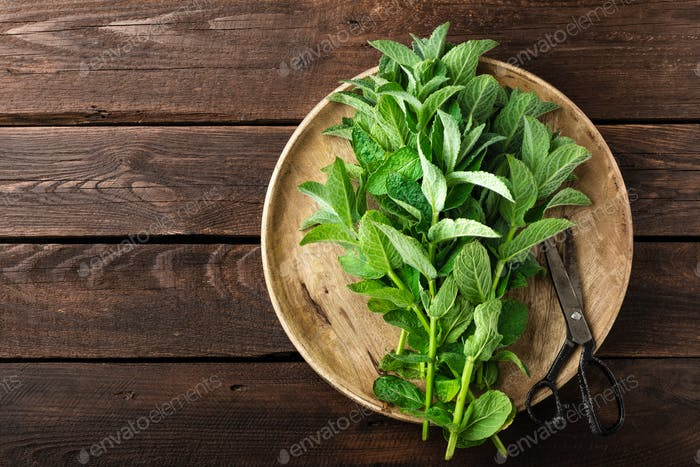 Fresh mint leaves on wooden rustic table, top view