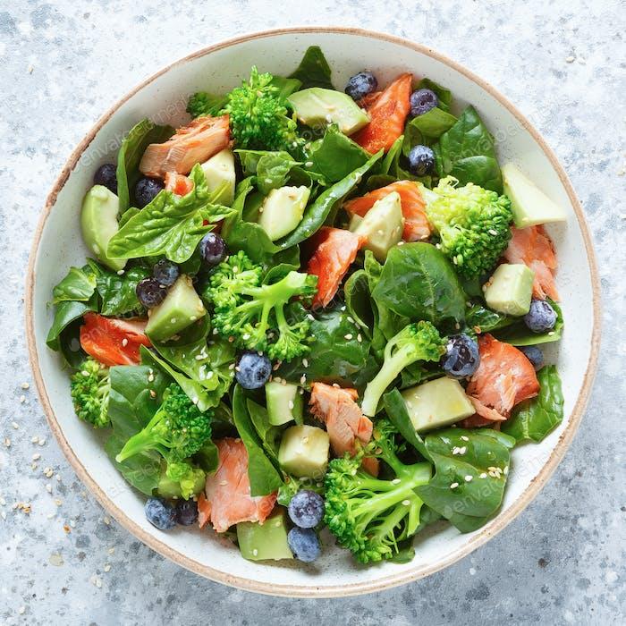 Lachsfisch und Avocado-Salat mit frischen Spinatblättern, Brokkoli, Heidelbeere mit Olivenöl gekleidet