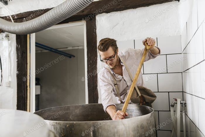Worker mixing ingredients in vat
