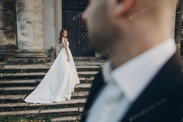 Gorgeous wedding couple posing on stone stairs near old castle