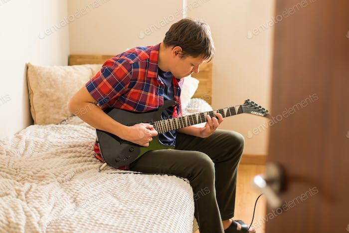 Millennial man playing, practicing electric guitar at home