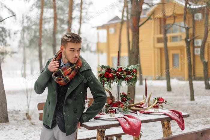Retrato de un novio barbudo en un traje elegante con tirantes y pajarita en invierno en una estación de esquí