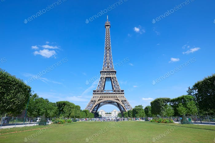 Eiffel Tower in Paris and empty green field of Mars meadow in a sunny summer day