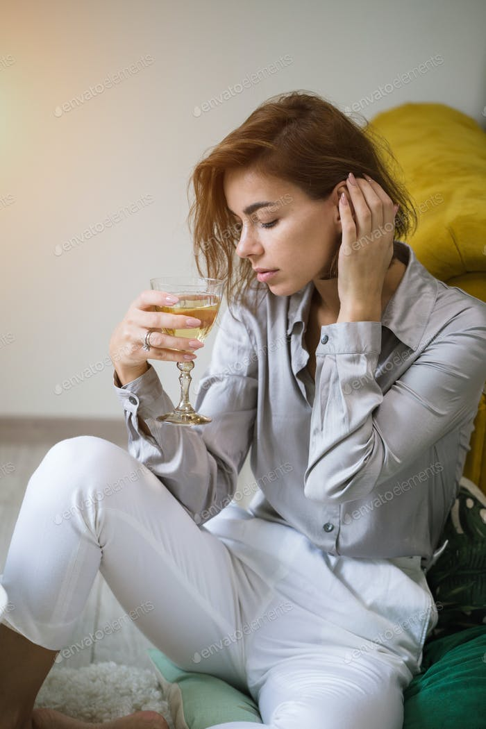 A beautiful young woman siting on a couch with a glass of wine