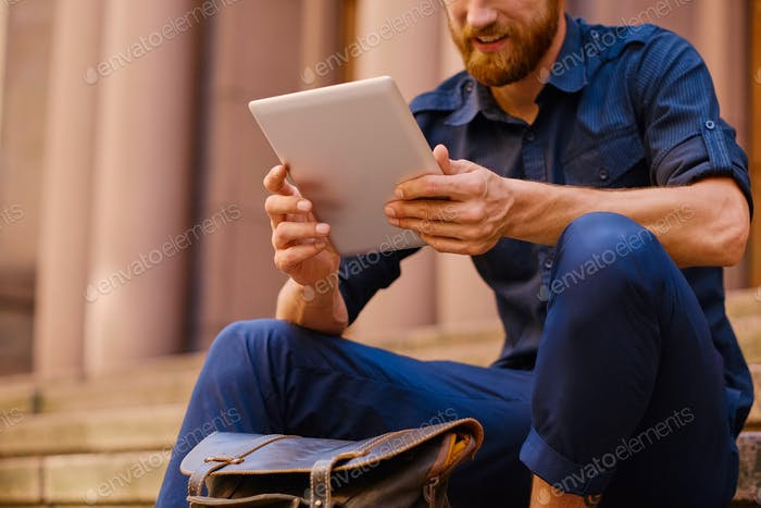 A man sits on a step and using a tablet PC.