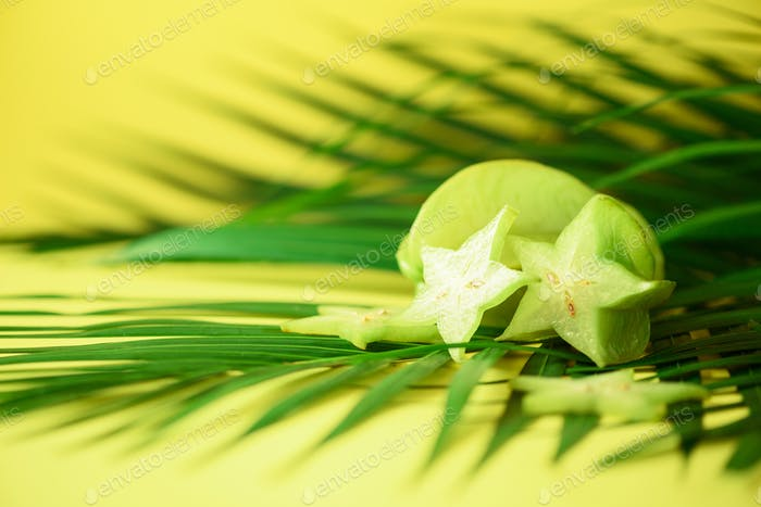 Exotic star fruit or averrhoa carambola over tropical green palm leaves on yellow background. Copy