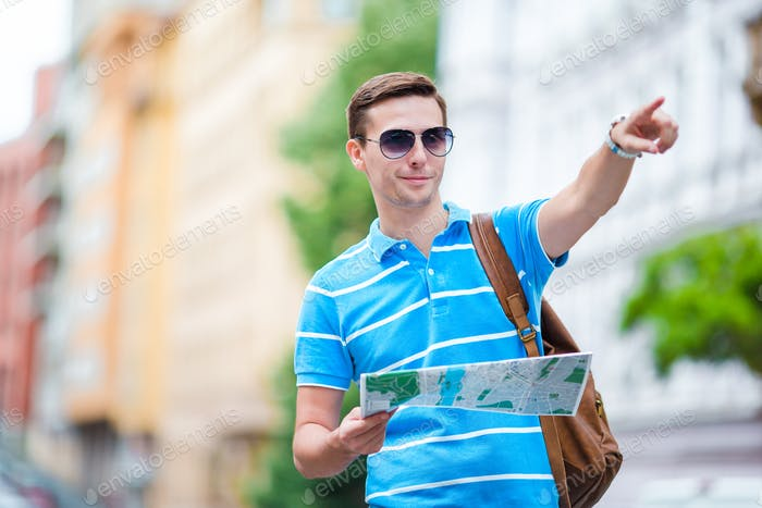 Man tourist with a city map and backpack in Europe. Caucasian boy looking at the map of European