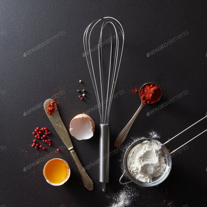 Spoon with red pepper, metal whisk, vintage knife raw egg and flour on a black concrete background