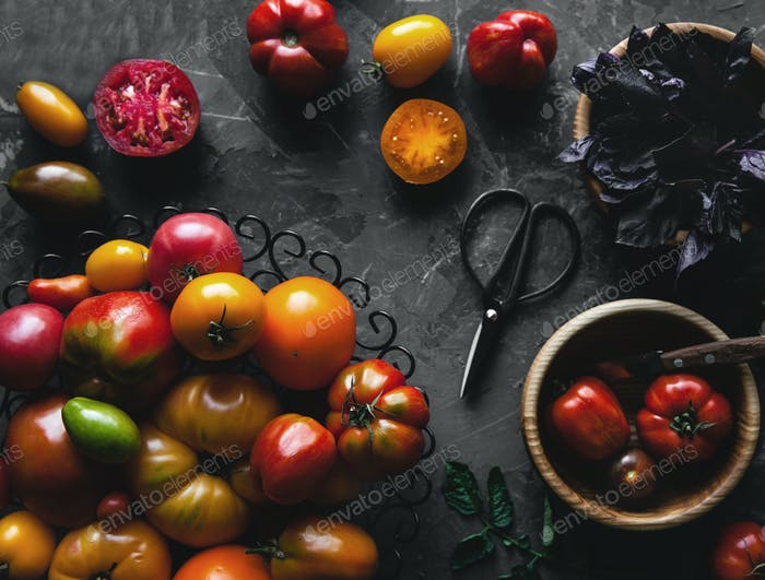 Composition with tomatoes, wooden board and products on grey background, healthy food, vegetables