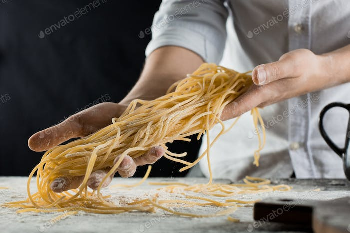Cook holding freshly cooked spaghetti in the kitchen