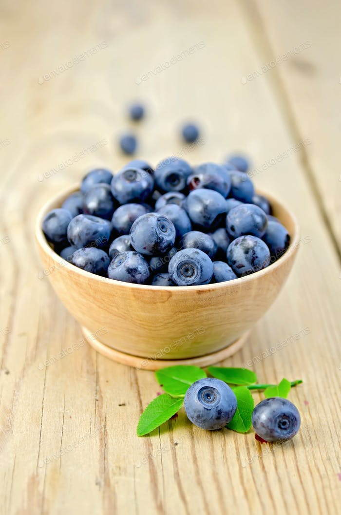 Blueberries in a wooden bowl on the board