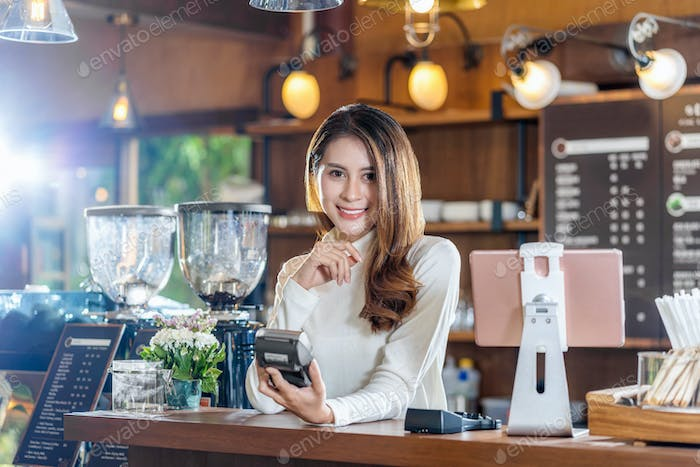 Asian Small business young owner holding contactless nfs technology machine to checking