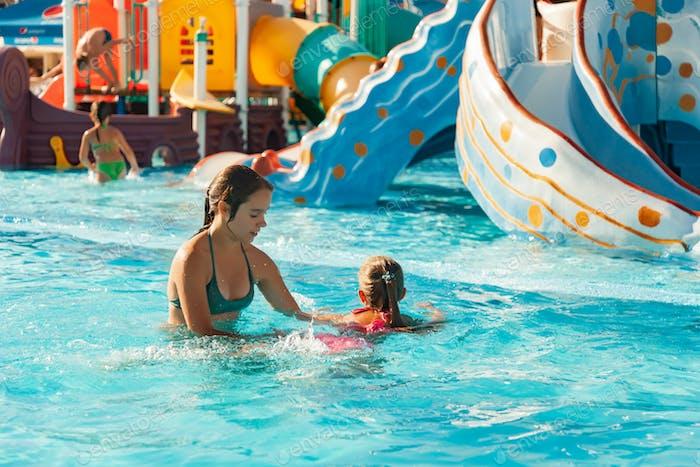 Сестра помогает научиться плавать в бассейне с чистой и прозрачной водой
