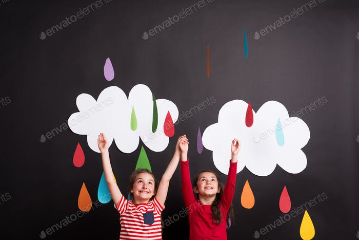 Small girls in studio, standing against black background with clouds and raindrops.