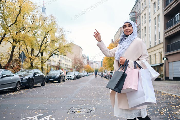 Young stylish Arabic woman in hijab with shopping bags trying to stop taxi on street