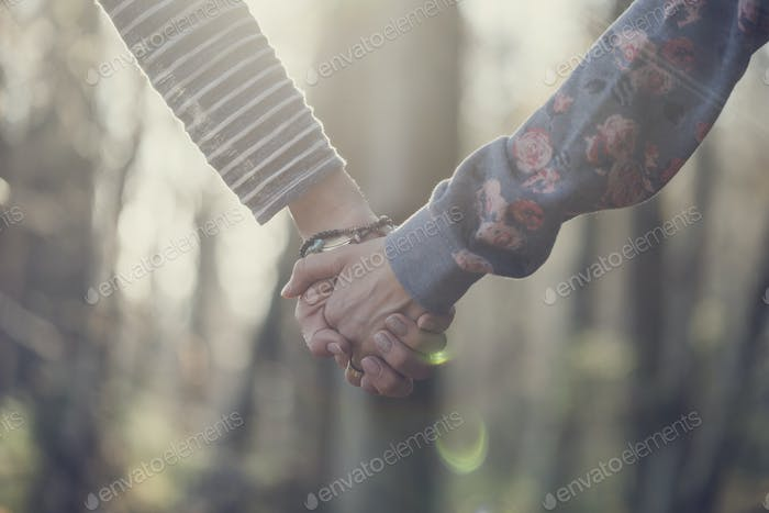 Toned image of two women holding hands
