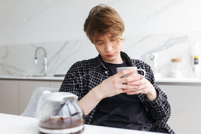 Young man sitting and sleeping with cup of coffee in hands in kitchen at home