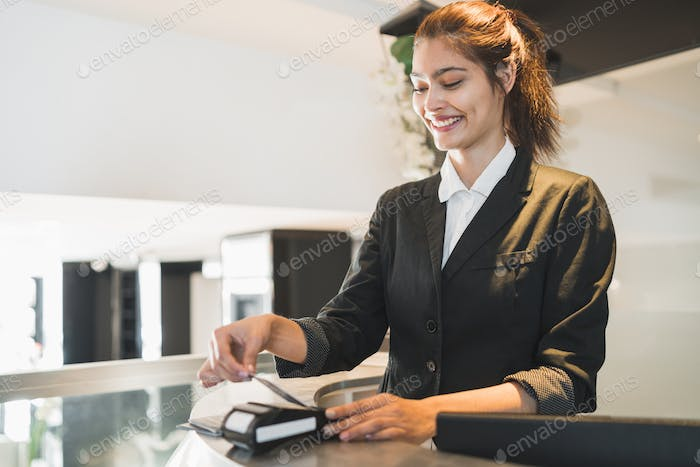 Receptionist passing card and charging guest stay at reception.