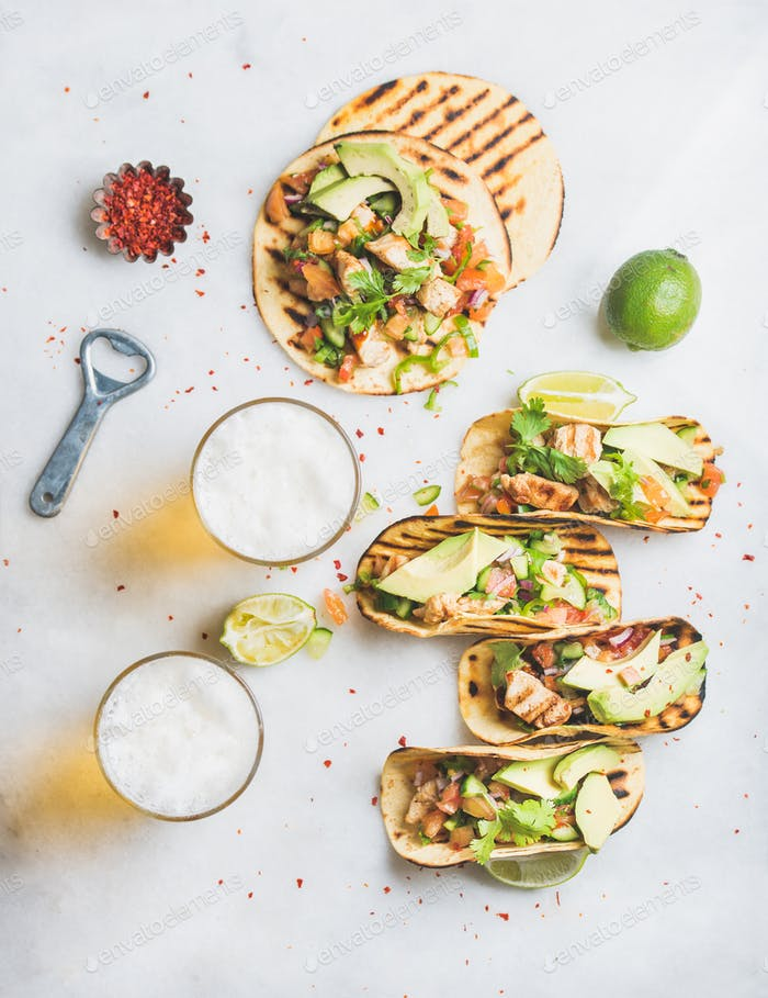 Healthy corn tortillas with chicken, vegetables, limes, beer in glasses