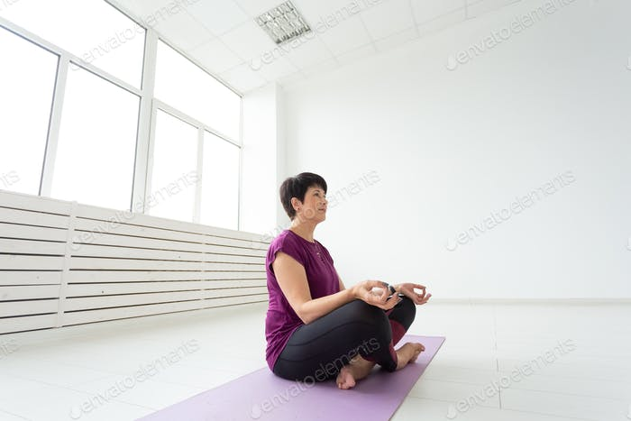 Harmony, people concept - middle aged woman doing yoga meditation