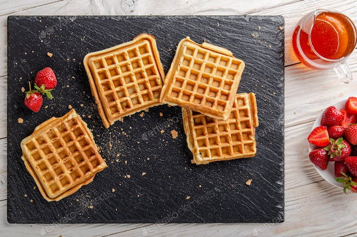 Homemade Belgian waffles on slate tray with maple syrup and strawberries aside. Flat lay view
