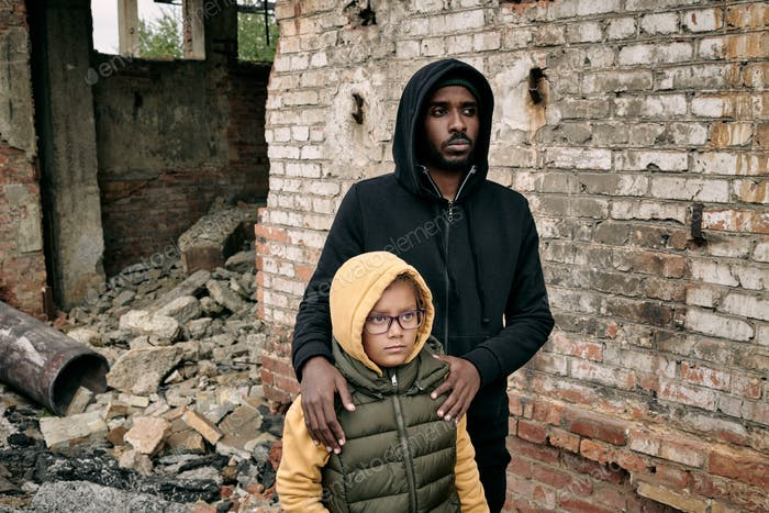 Black Man With Daughter At Ruined House
