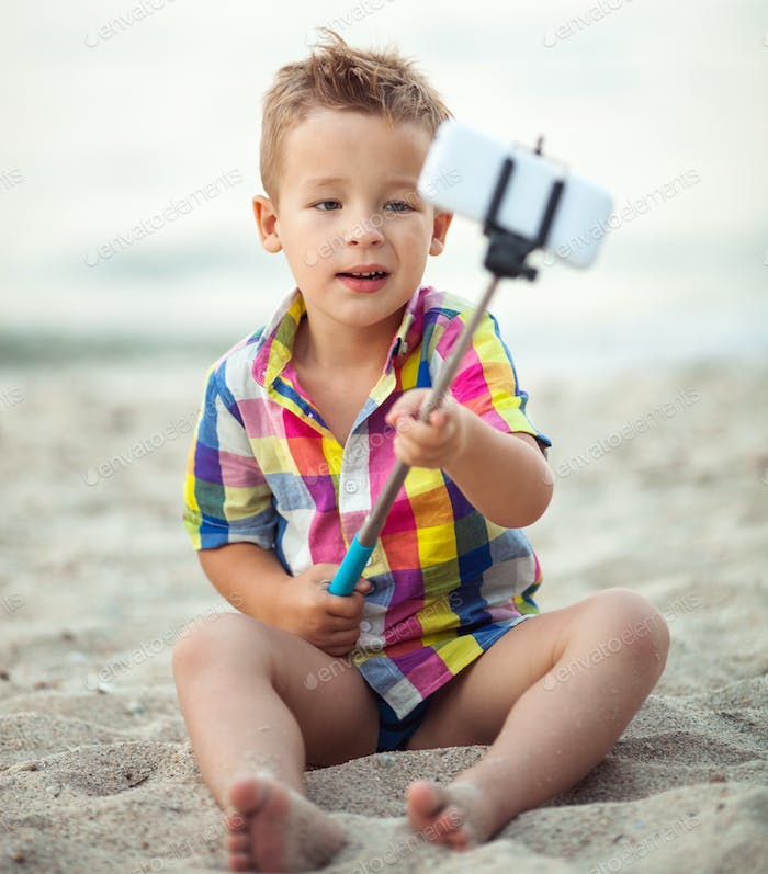 Child with phone and selfie stick on the beach
