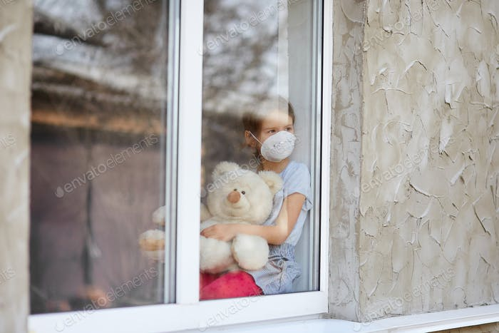 Sad Child, little girl in mask with teddy bear looking from window, coronavirus quarantine