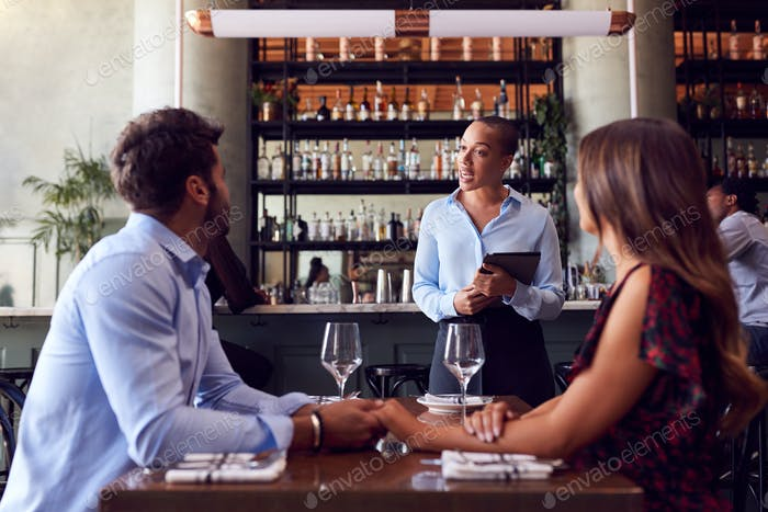 Female Waitress With Digital Tablet Taking Order From Romantic Couple Sitting At Restaurant Table