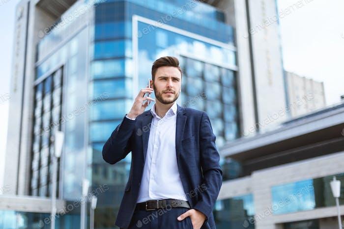 Serious millennial businessman speaking on smartphone near skyscraper at street
