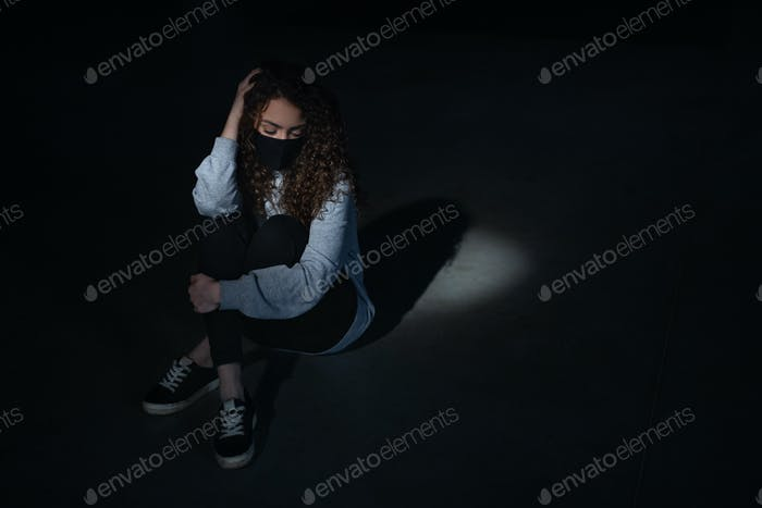 Top view portrait of depressed young woman indoors, covid-19 and mental health concept