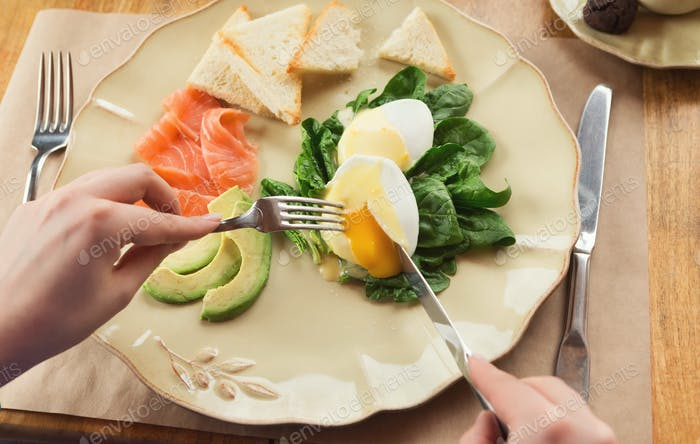 Woman having healthy breakfast with poached eggs and smoked salm