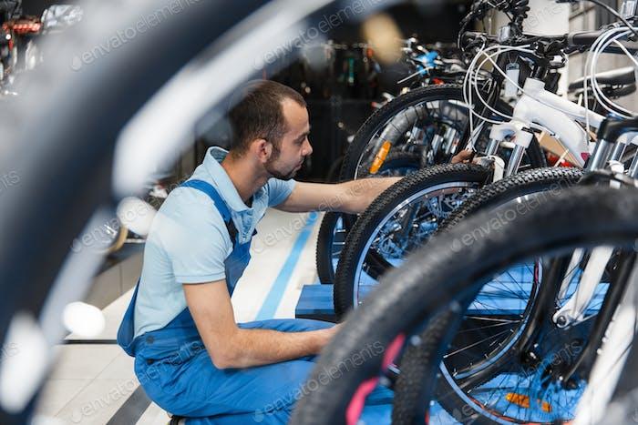 Bicycle shop, repairman looking on new bike