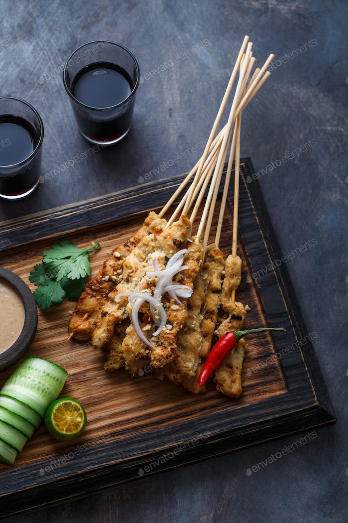 Close view of malaysian chicken skewers - satay or sate ayam with peanut sauce, dark background