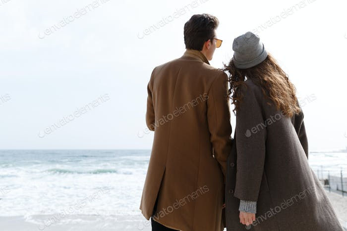 Back view of couple enjoying the view on the beach