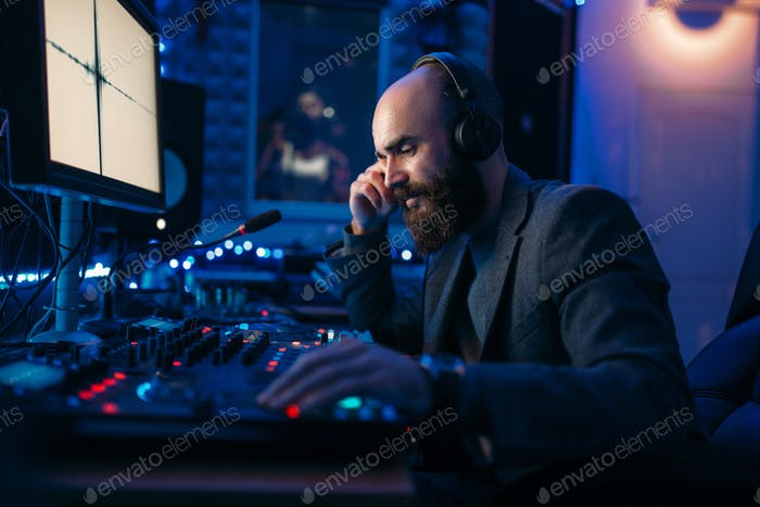 Sound engineer in headphones listens composition