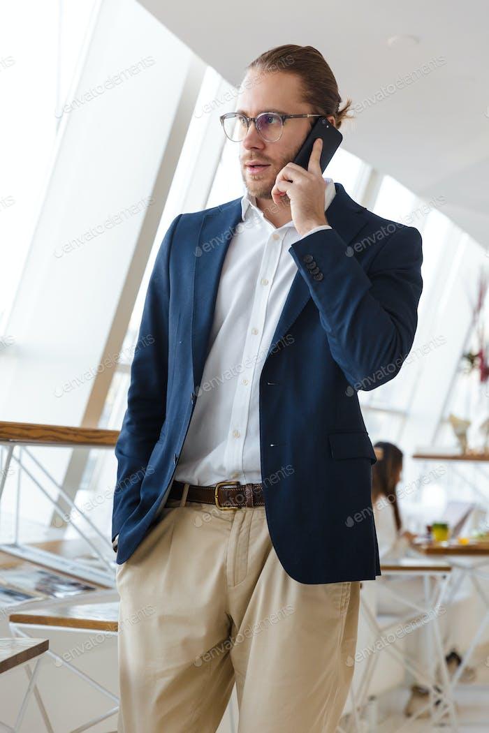 Geschäftsmann drinnen im Büro im Gespräch per Handy.