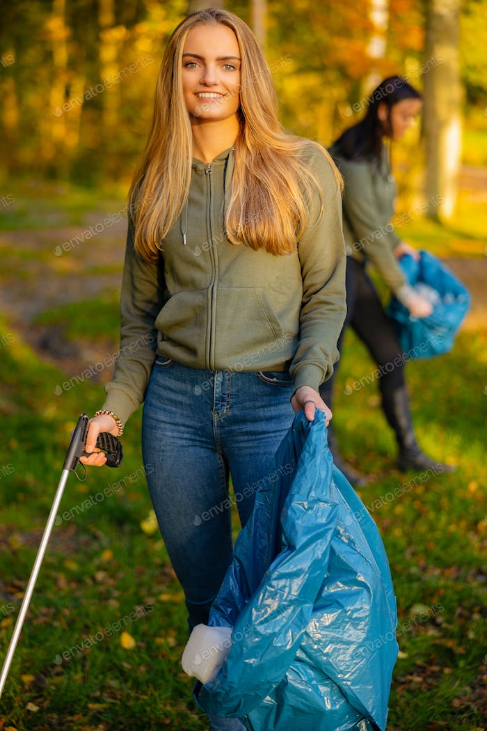 Young female volunteer holding garbage bag at park