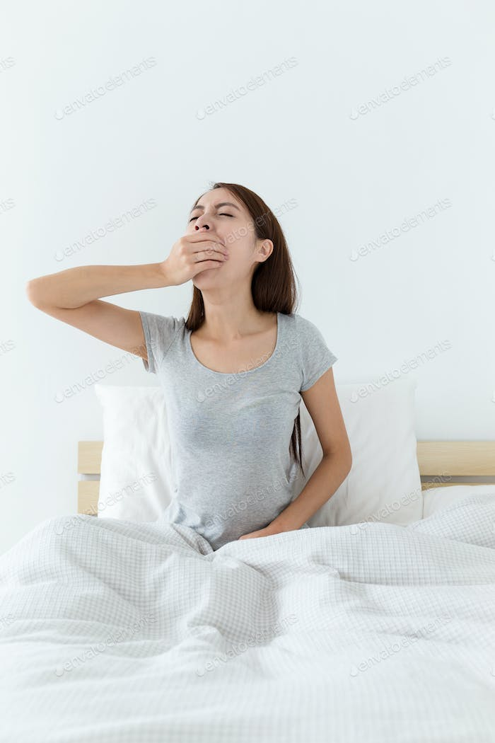 Young lady wake up and yawning on bed