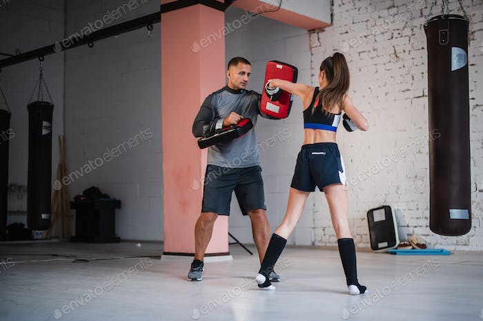 A girl boxer in sportswear practices a hook on the paw with a trainer