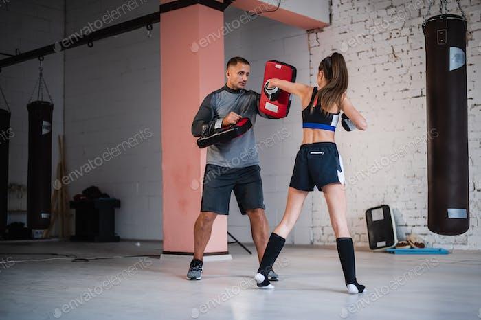 Ein Mädchen Boxer in Sportbekleidung praktiziert einen Haken an der Pfote mit einem Trainer