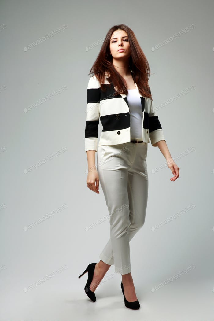 Full-length portrait of a young beautiful woman in casual clothes on gray background