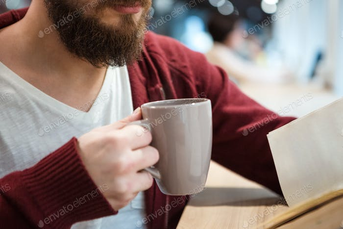 Young man holding a cup of hot drink and reading