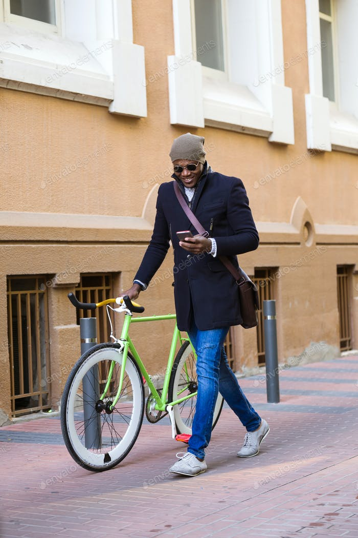 Handsome young man using mobile phone and fixed gear bicycle in