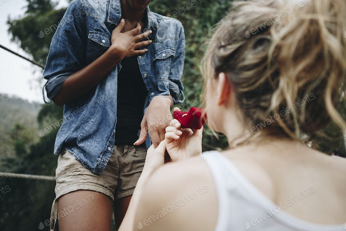 Woman proposing to her happy girlfriend outdoors love and marriage concept