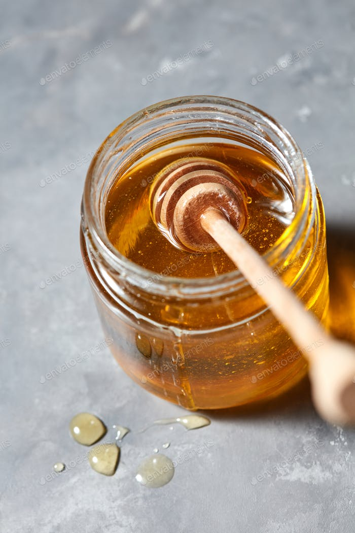 Wooden stick in a glass jar with fresh natural organic honey on a gray concrete table. Jewish New