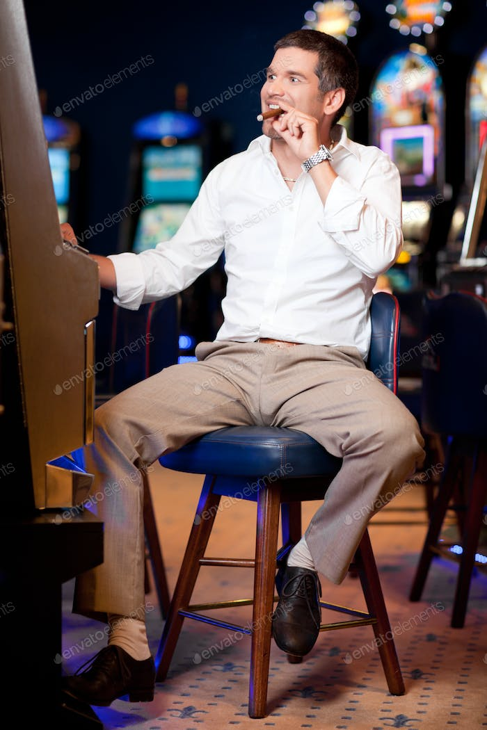 men with cuban cigar playing the slot machine