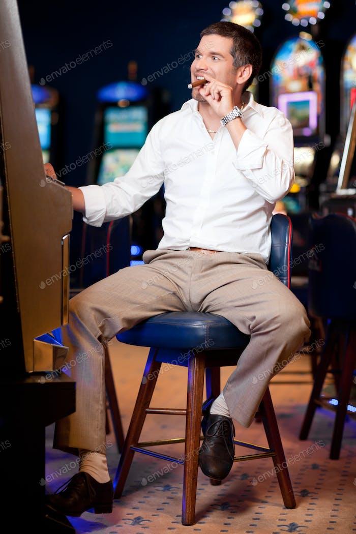 Männer mit kubanischen Zigarre spielen den Spielautomaten